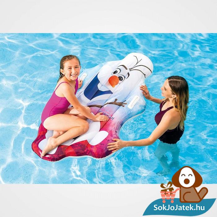Olaf alakú felfújható strand matrac a Jégvarázs Meséből ahogyan a vízen úszik egy kislánnyal..